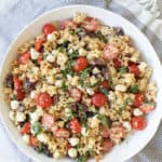 The best pasta salad recipe with cherry tomatoes, olive oil, cheese, olives, garlic and basil.