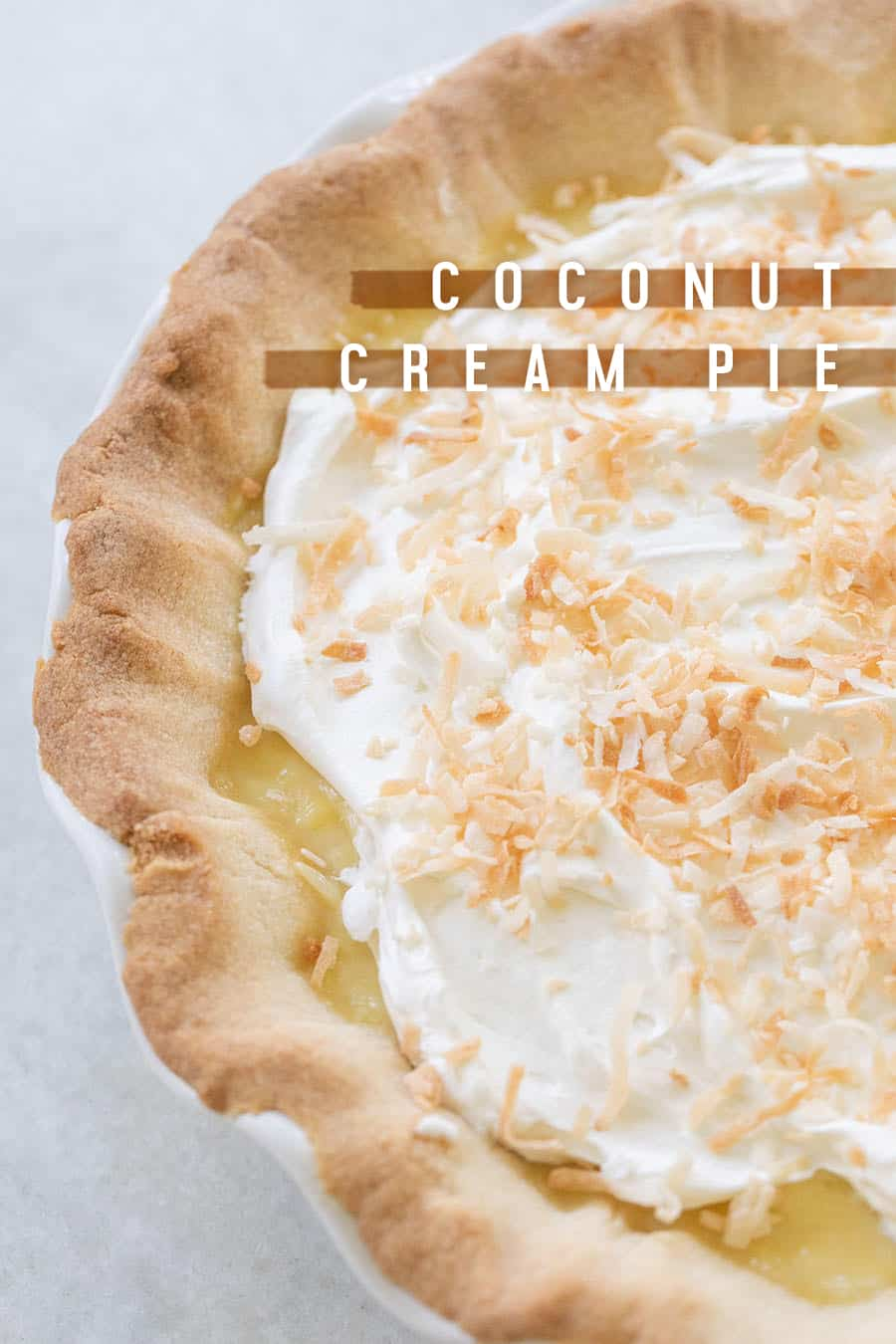 Coconut cream pie close up with whipped cream and toasted coconut.