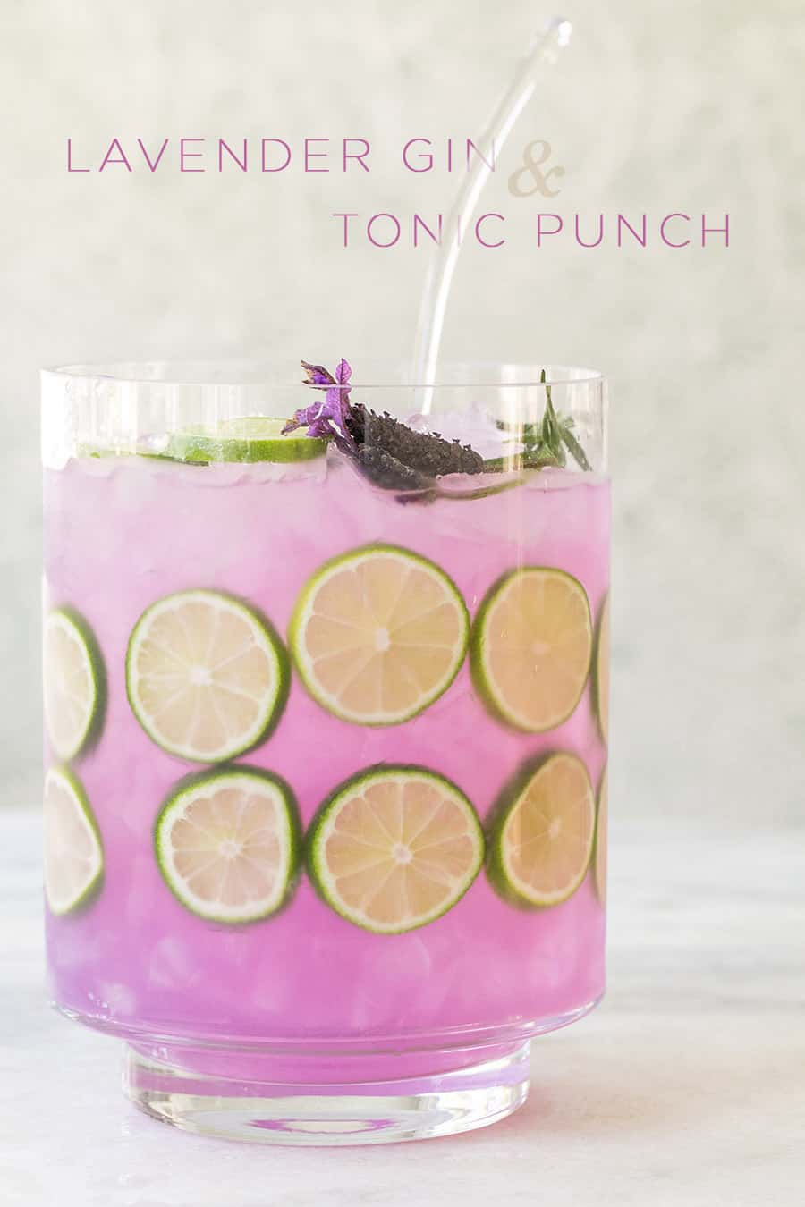 Purple gin and tonic punch with lime slices in a punch bowl.