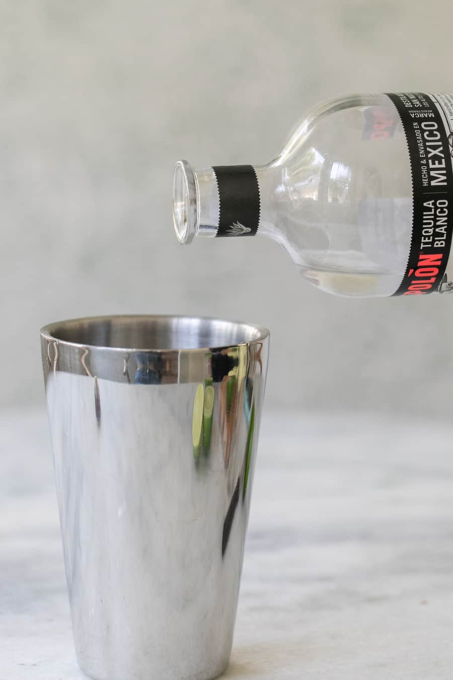 Pouring tequila into a cocktail shaker.
