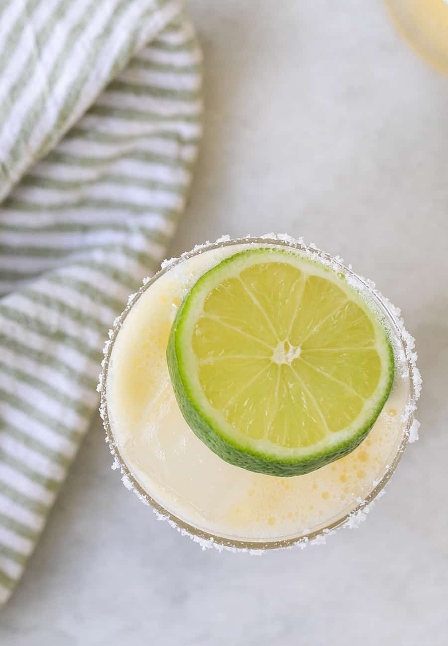 Overhead photo of a skinny margarita with a lime wedge on a marble table.