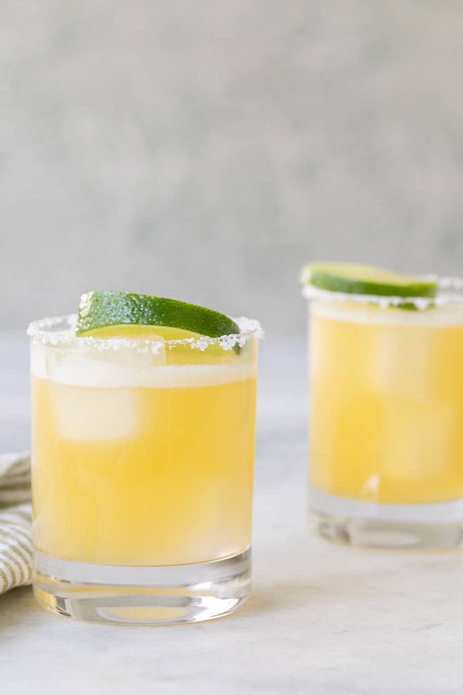 Two margaritas with salted rims and lime wedge.