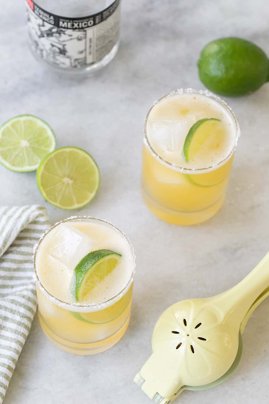Margaritas with lime wedges on a marble table.