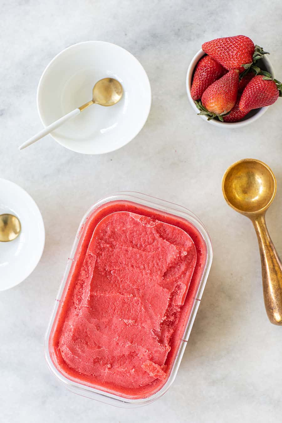 Elderflower strawberry sorbet with a gold ice cream scooper.