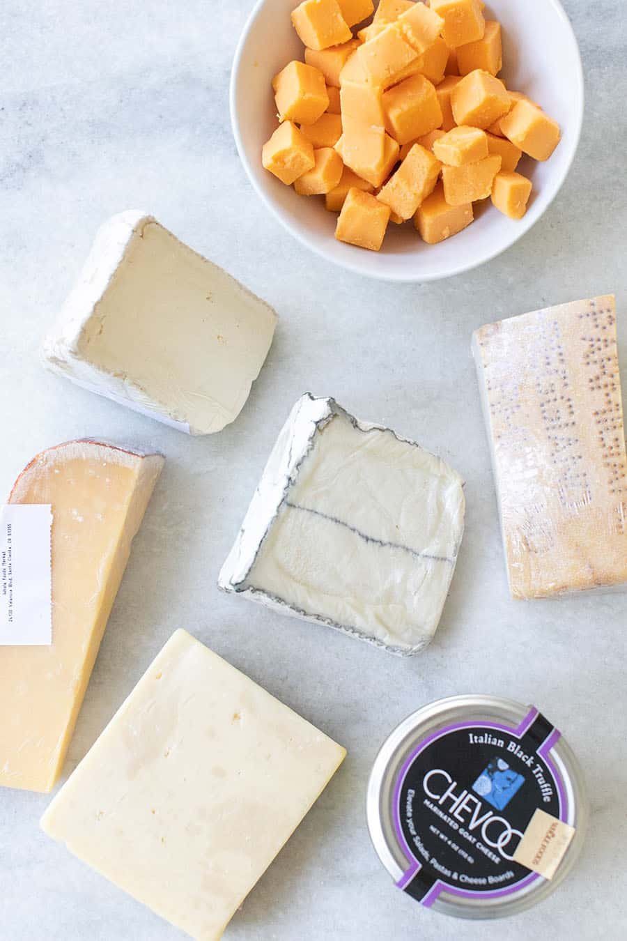 Overhead of different cheeses for cheese board.