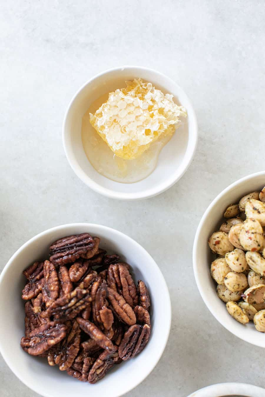 Honey comb in a white bowl with almonds and walnuts