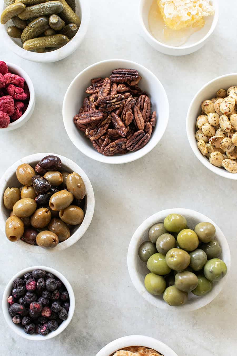 overhead of nuts, olives and dried berries on a marble table.
