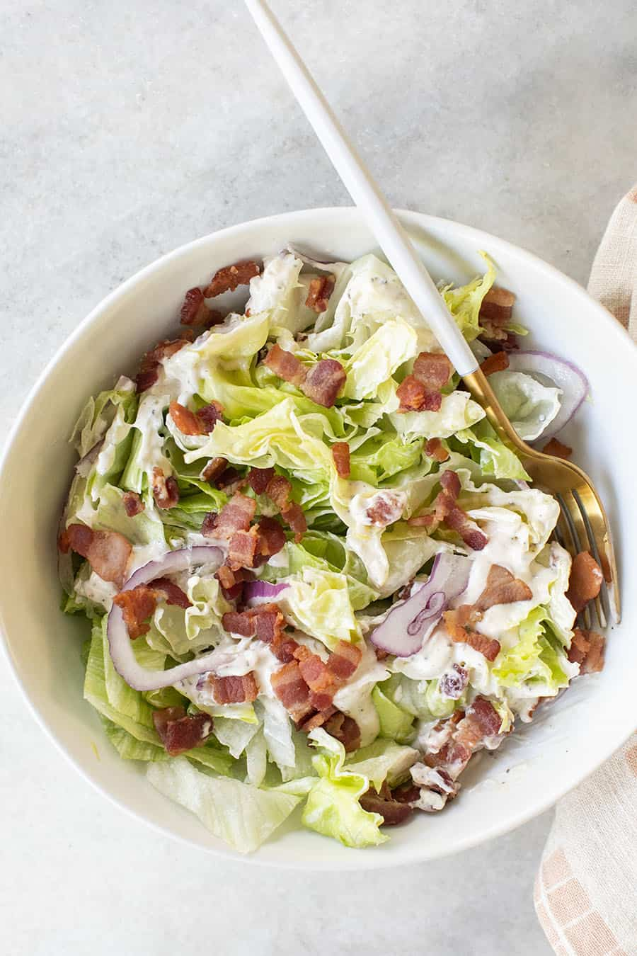 Wedge salad chopped in a white bowl.