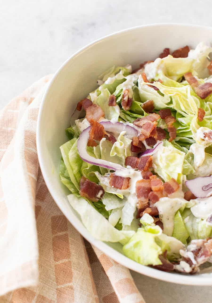Chopped wedge salad with bacon, onions and dressing.
