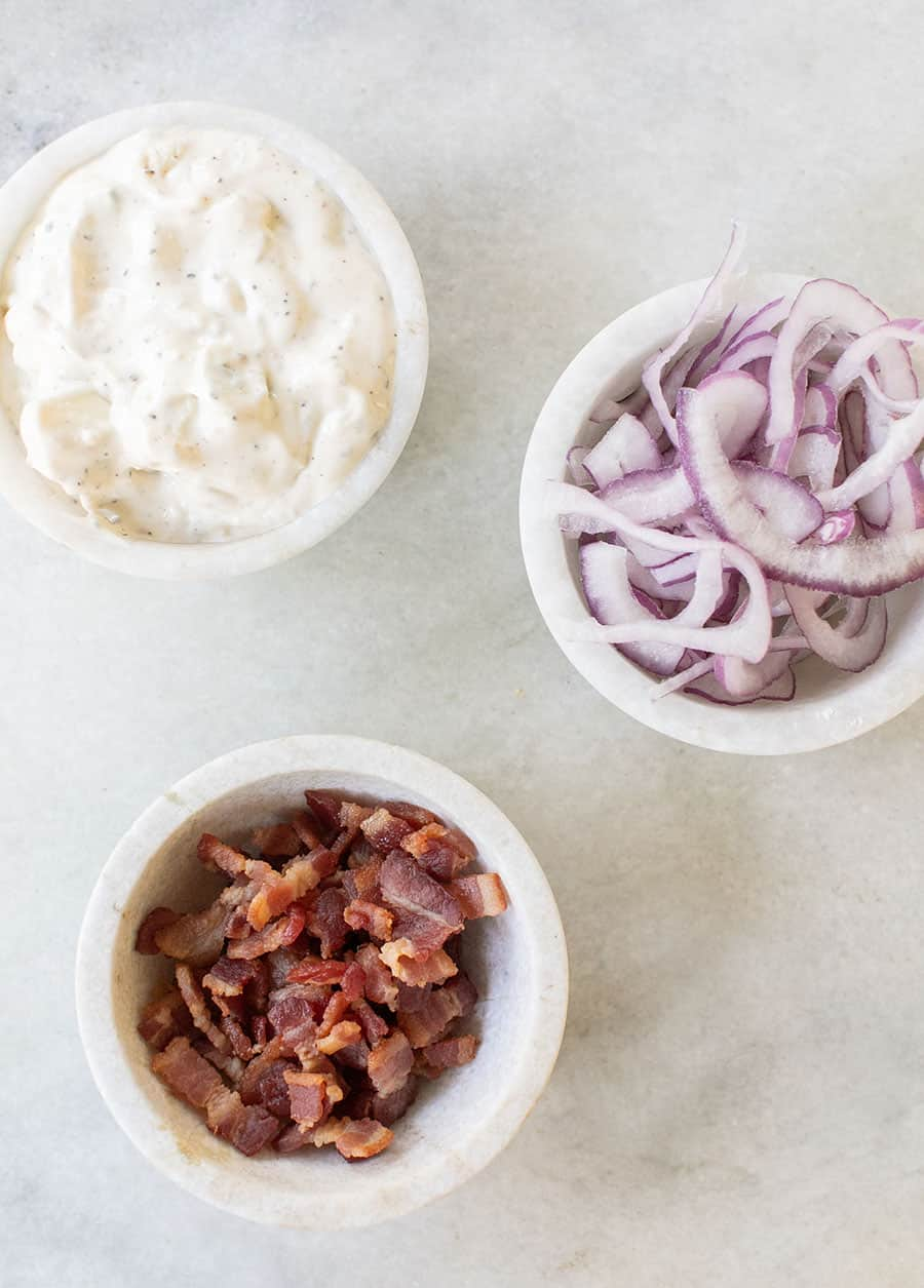 Bacon, blue cheese dressing and onions in marble bowls for a classic wedge salad.