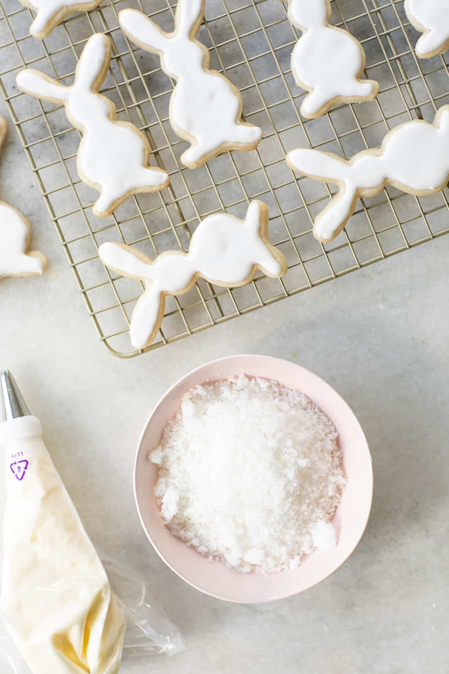 Easter cookies shaped as bunnies on a cooling rack with a bowl of coconut.