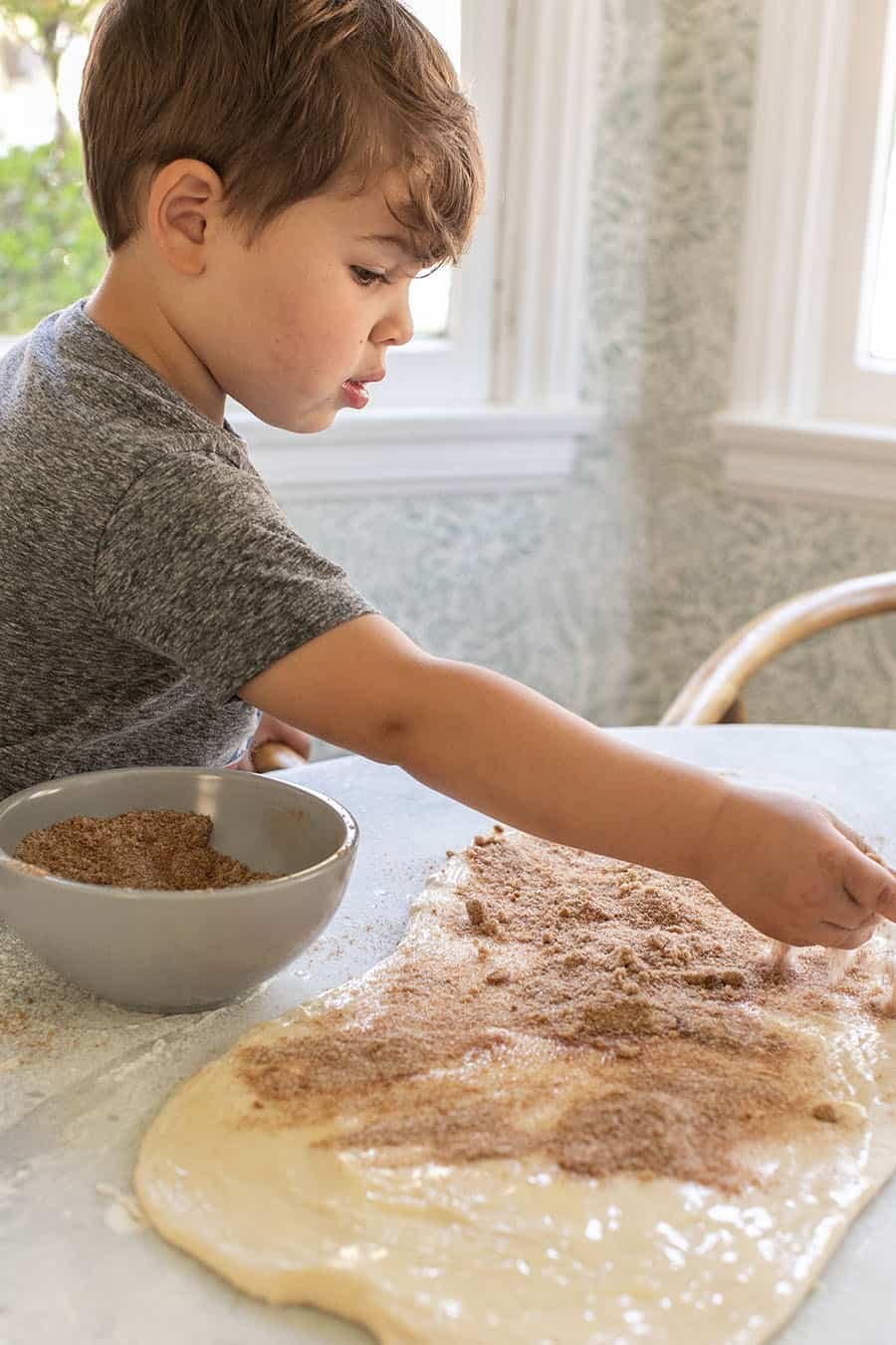 Little boy making cinnamon rolls