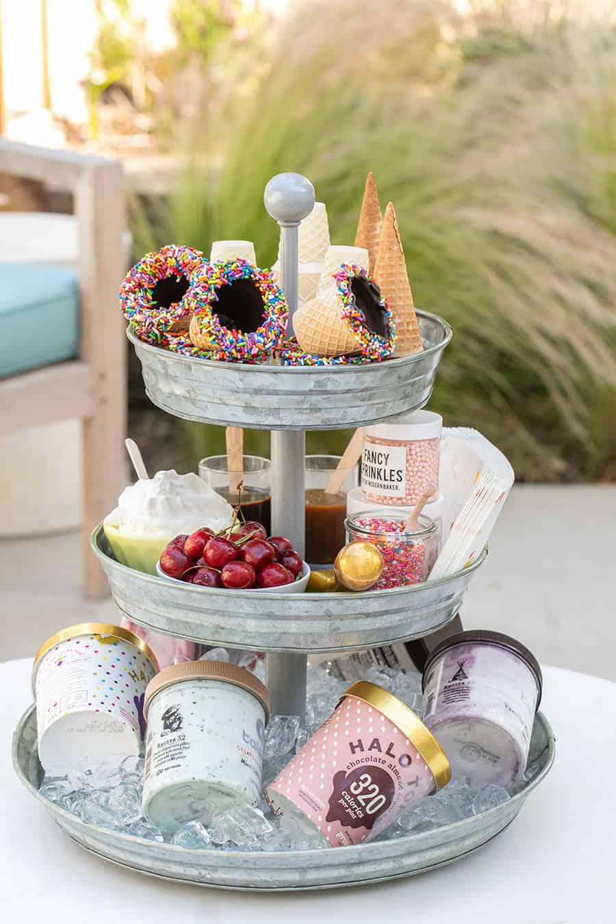 Tiered Galvanized Tray with ice cream cones on top. cherries and toppings in the center and ice cream on the bottom.