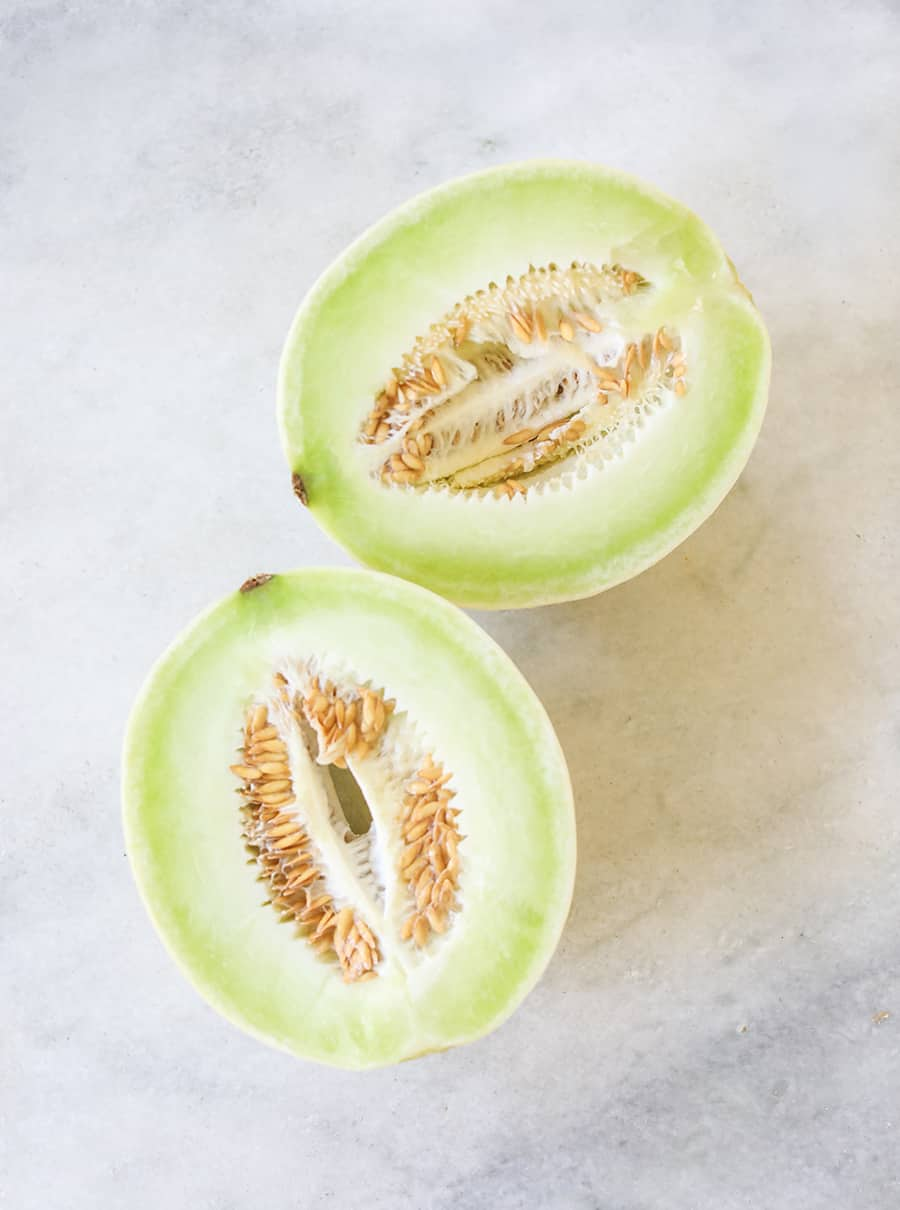 Honeydew cut in half on a marble table.