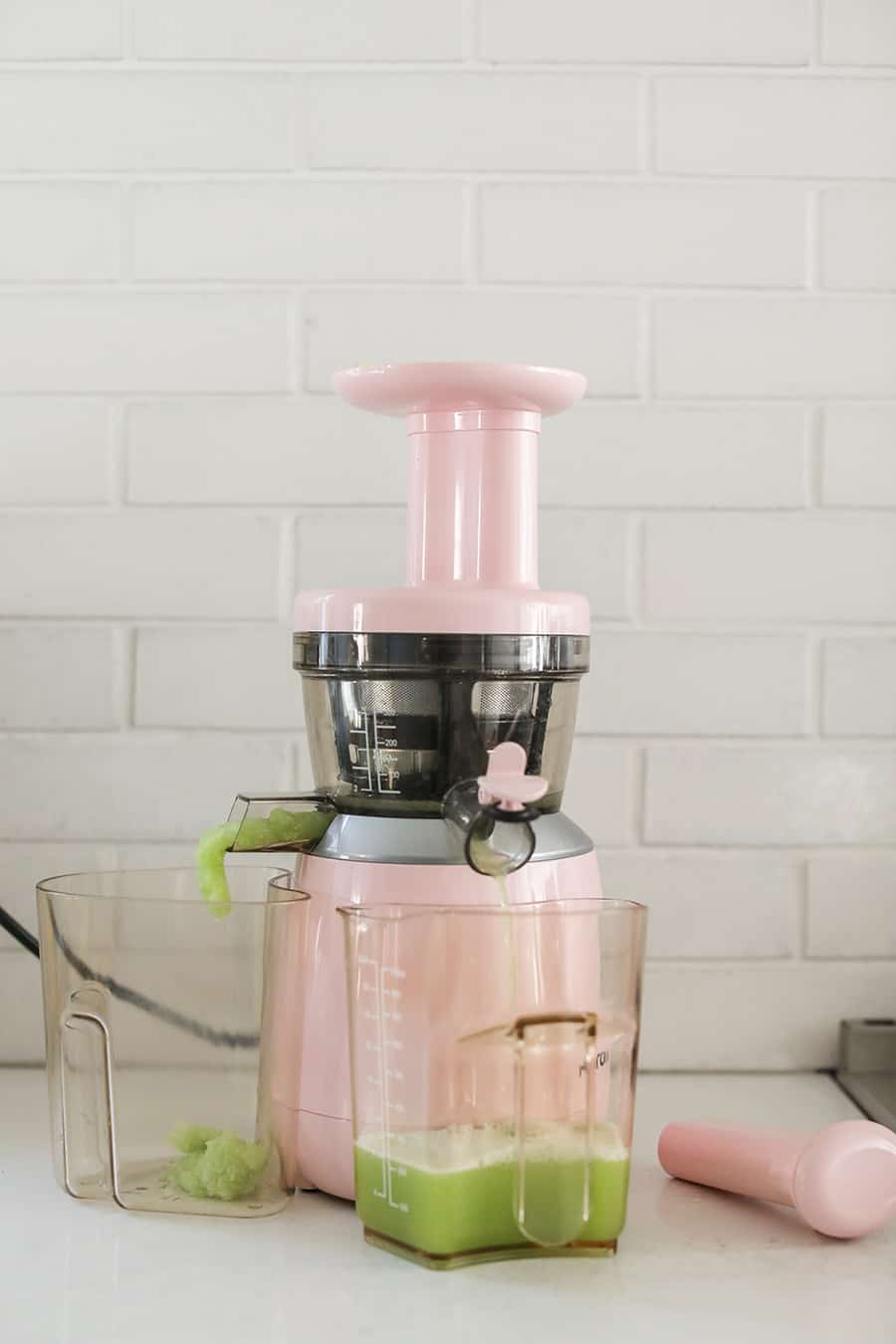 Making juice in a pink juicer.