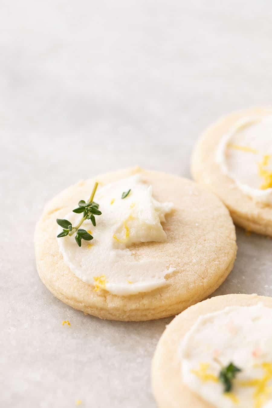 Lemon & Thyme Shortbread Cookie with a little lemon frosting and a sprig of thyme.