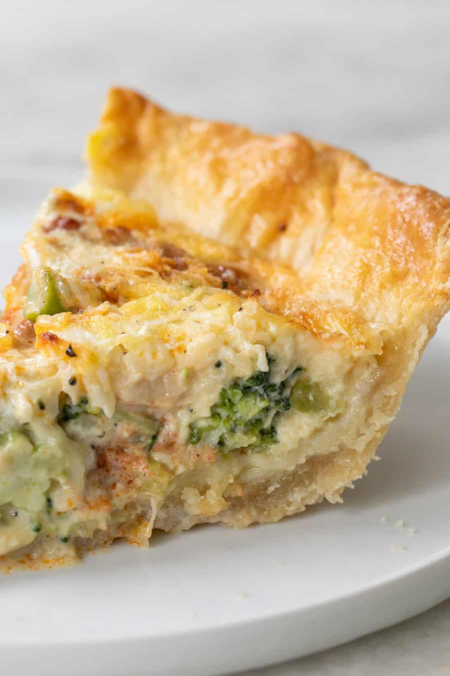 slice of a quiche with layers of cheese and broccoli