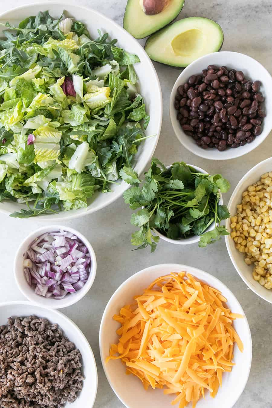 Ingredients for a taco salad, lettuce, onions, cheese, beans, ground beef, corn.