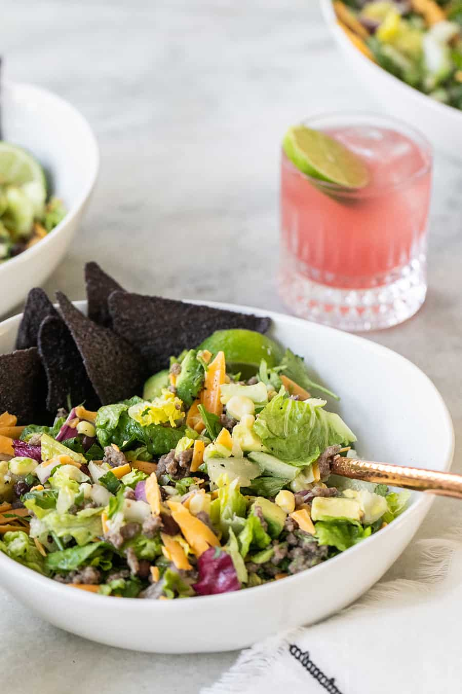 Taco salad bowl with blue chips and margaritas.