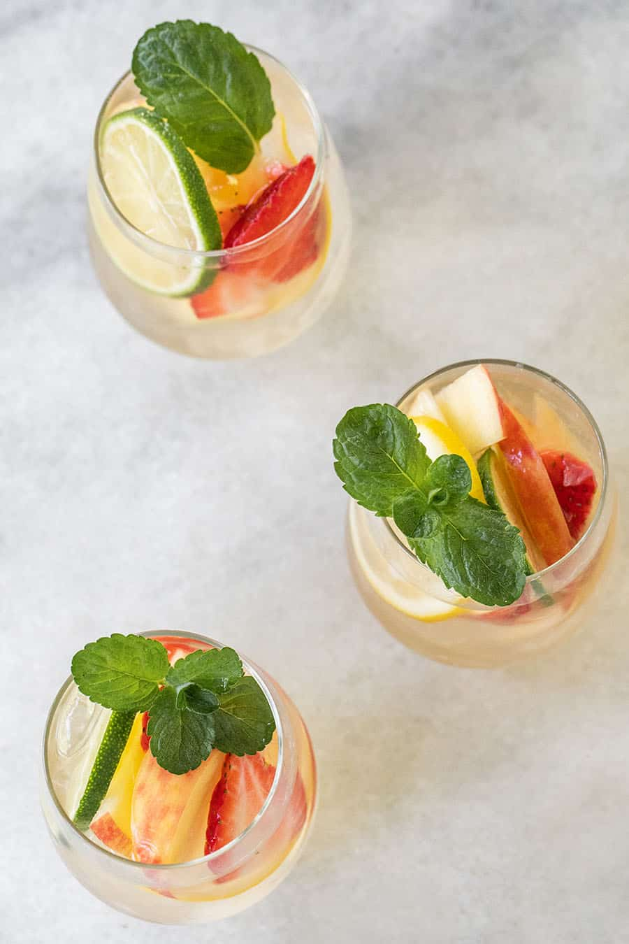 Three glasses of white wine sangria with fresh mint.
