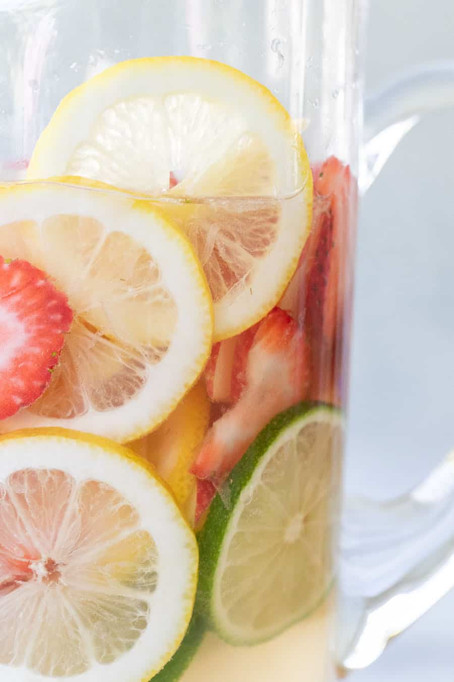 White wine sangria recipe with lemon and lime slices and strawberries.
