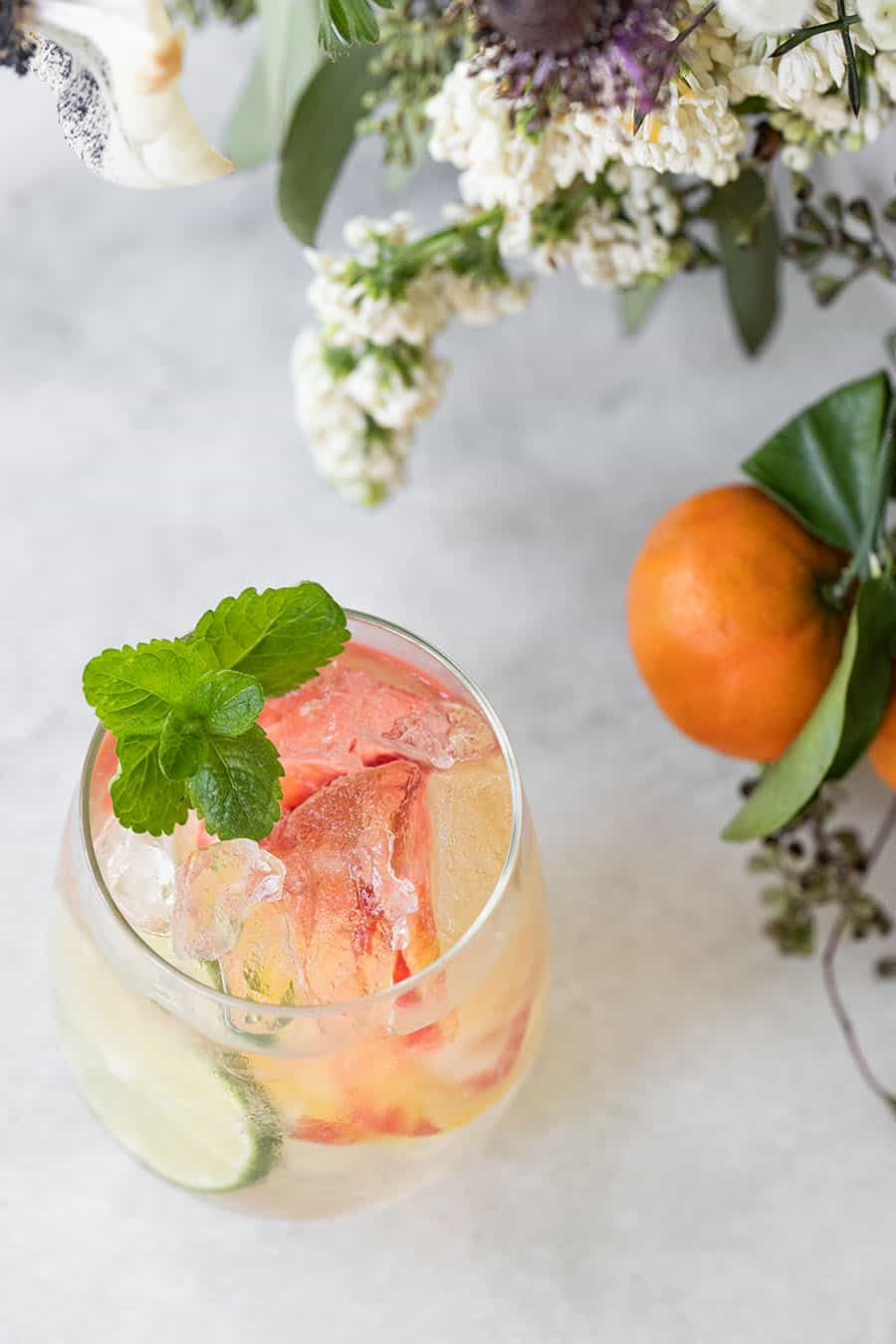 Glass of white wine sangria with fresh mint and flowers.