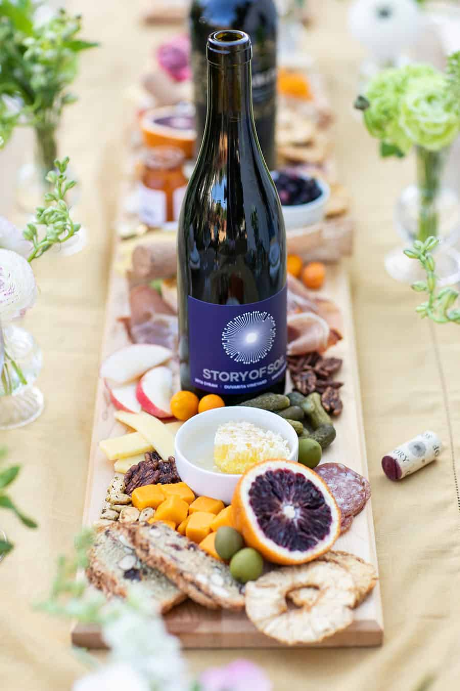 Story of Soil red wine bottle on a board with cheese and fruit.
