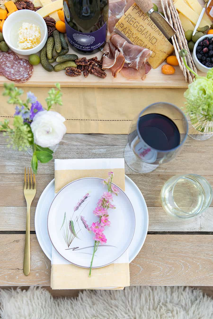 table setting with wine glass and yellow table runner.