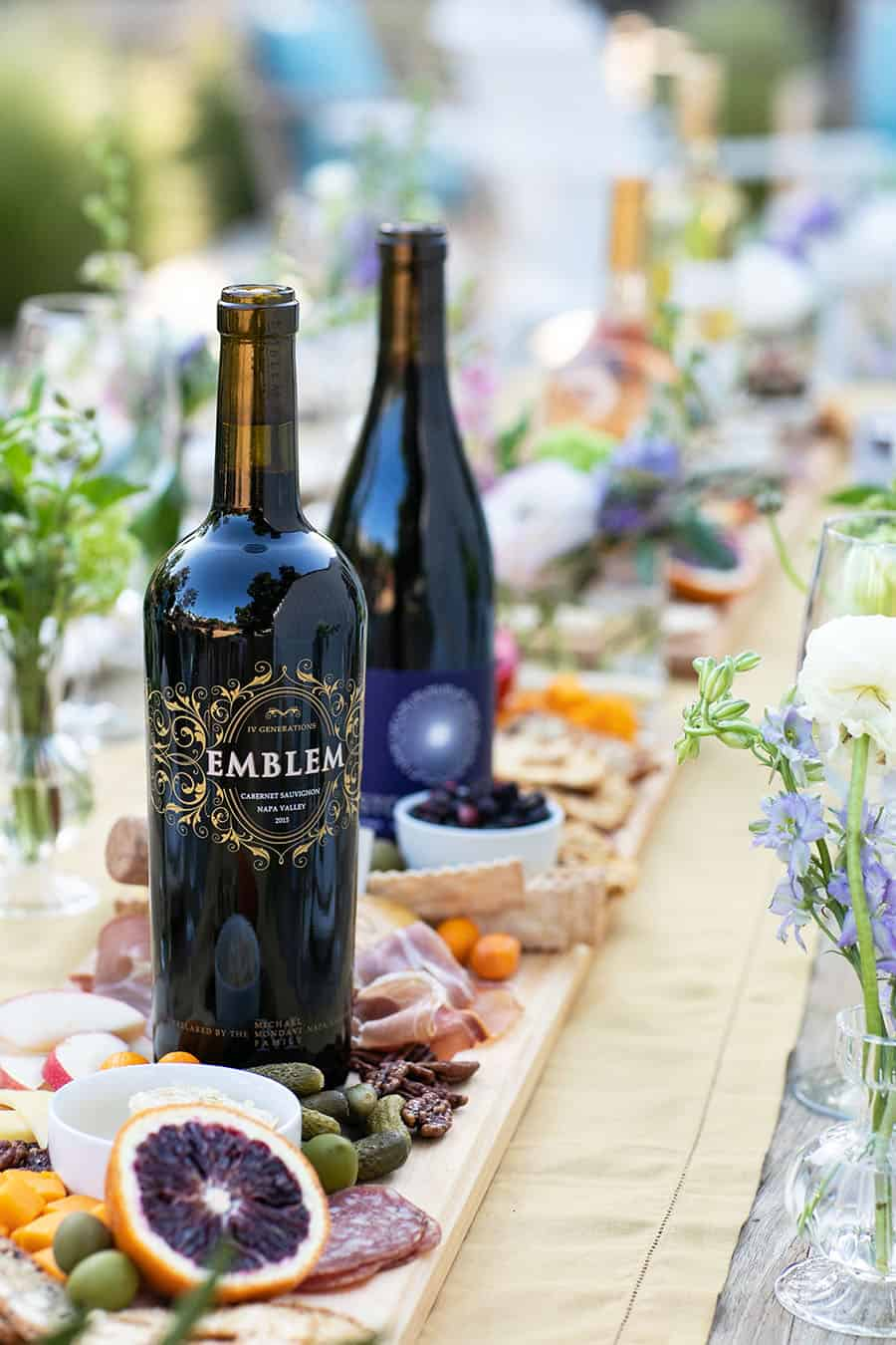 Bottle of Emblem wine on a cheee board with cheese and fruit.