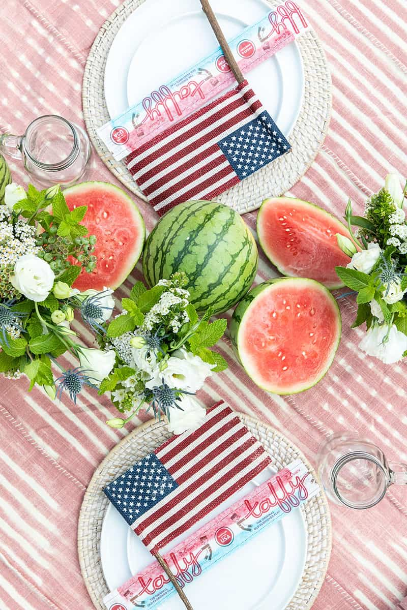 Table set for 4th of July party with watermelon down the middle, flags on table settings, mugs, pink table cloth.