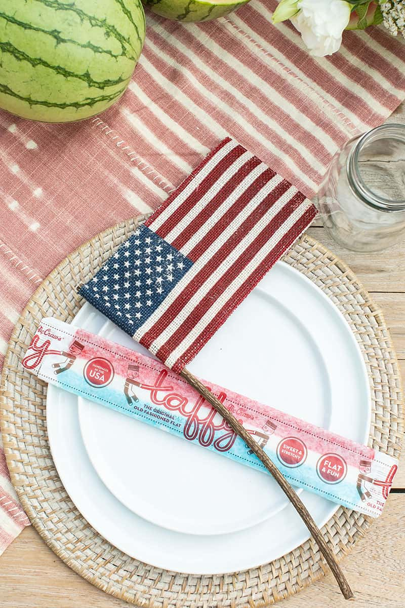 White plates on woven charger with burlap flags and large old-fashioned taffy.