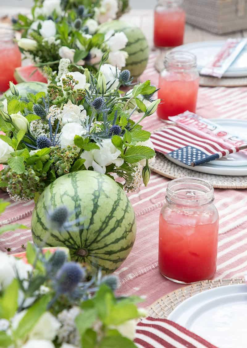 Watermelon, flower arrangements and a jar full of watermelon juice