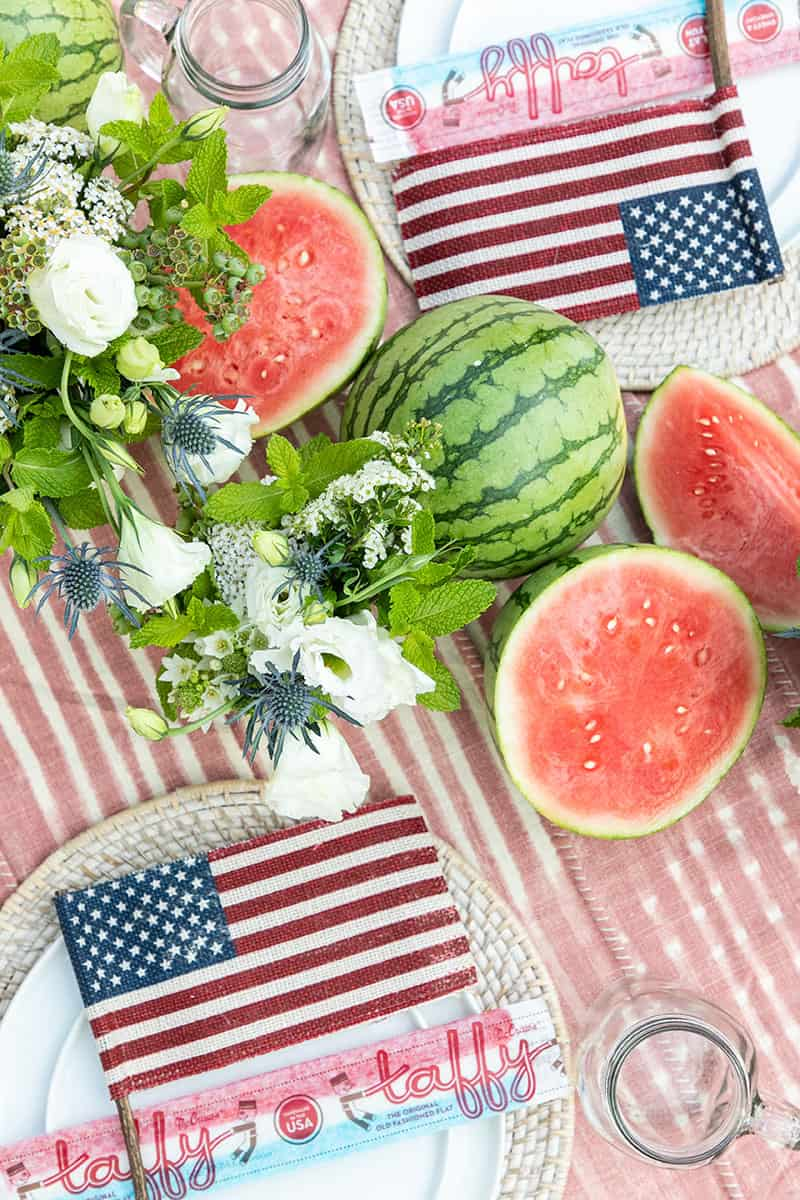 4th of July party table setting with flowers, watermelon, burlap flag and taffy.