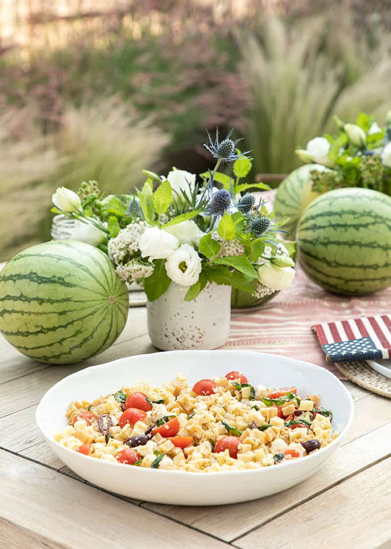 Pasta salad on a table with watermelons and a flower arrangement