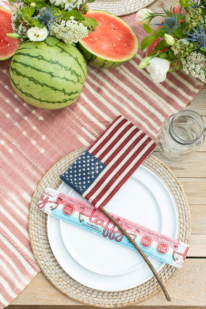 4th of July party table setting with white plates on a woven charger and a burlap flag.