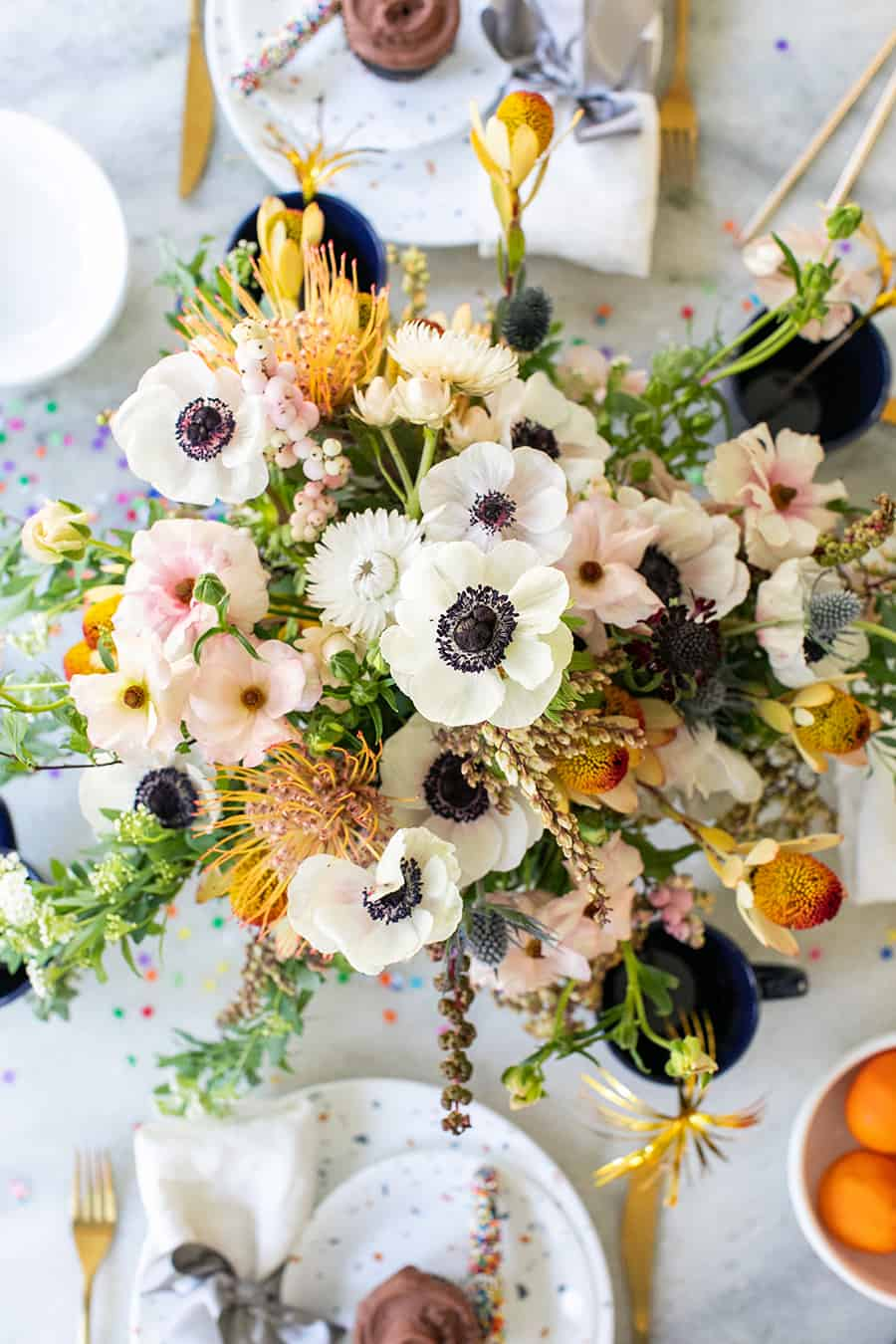Beautiful floral arrangement on a marble table with plates and cupcakes.