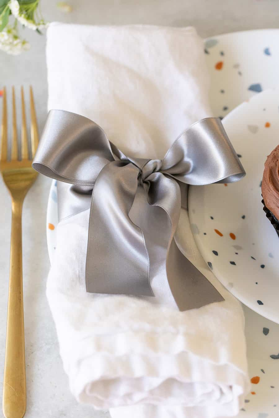 White napkin with a silver ribbon tied around it.