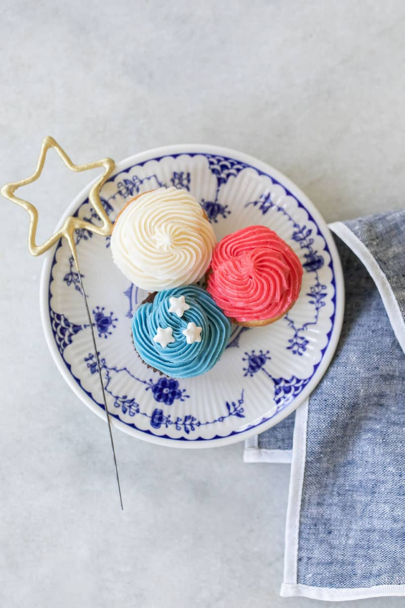 three mini red, white and blue cupcakes on a blue plate with a star sparkler.