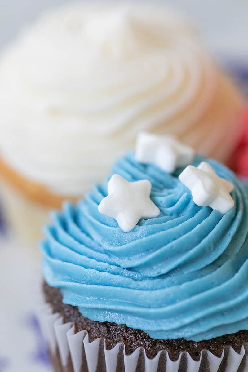 Mini cupcake with blue frosting and white sprinkle stars/