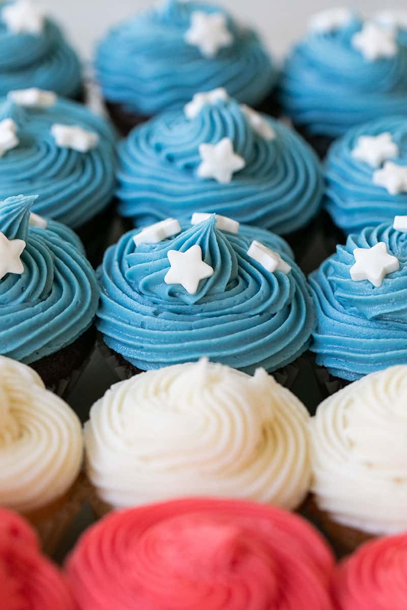 Mini cupcakes with blue and white and red frosting.