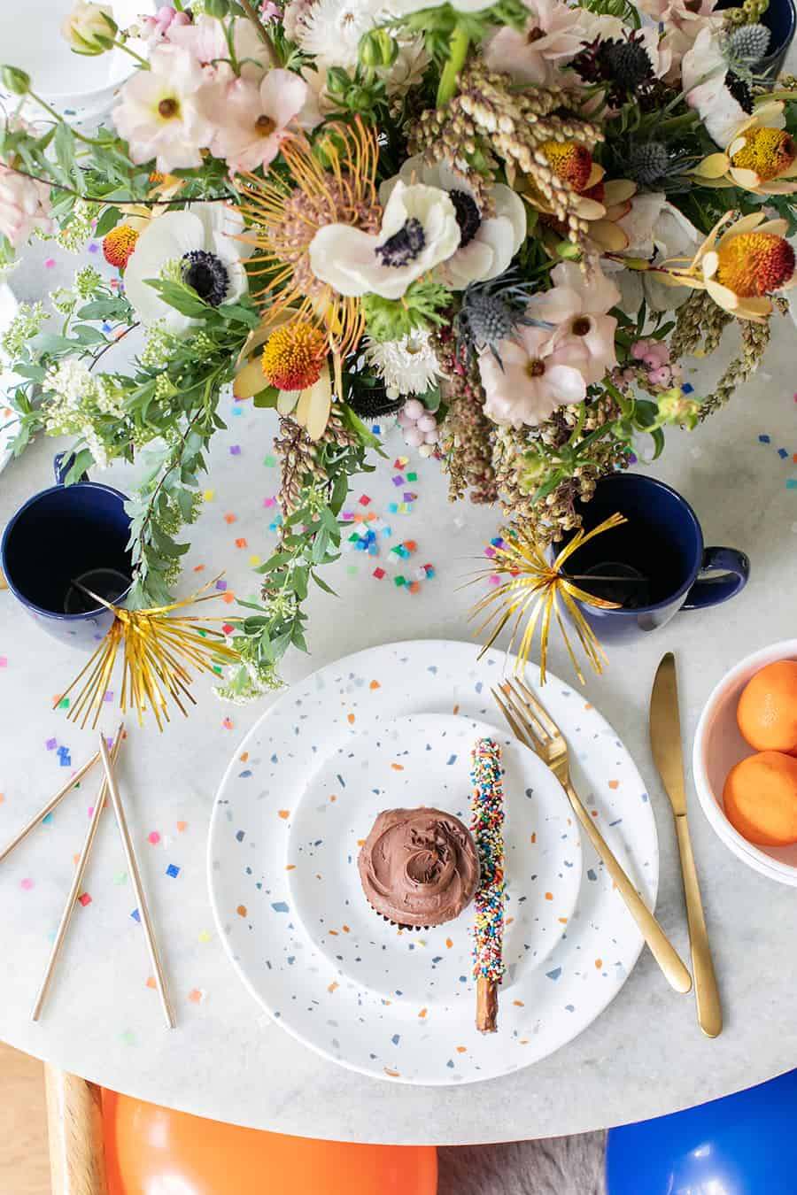 A birthday party set-up with flowers, cupcake, plates and confetti.
