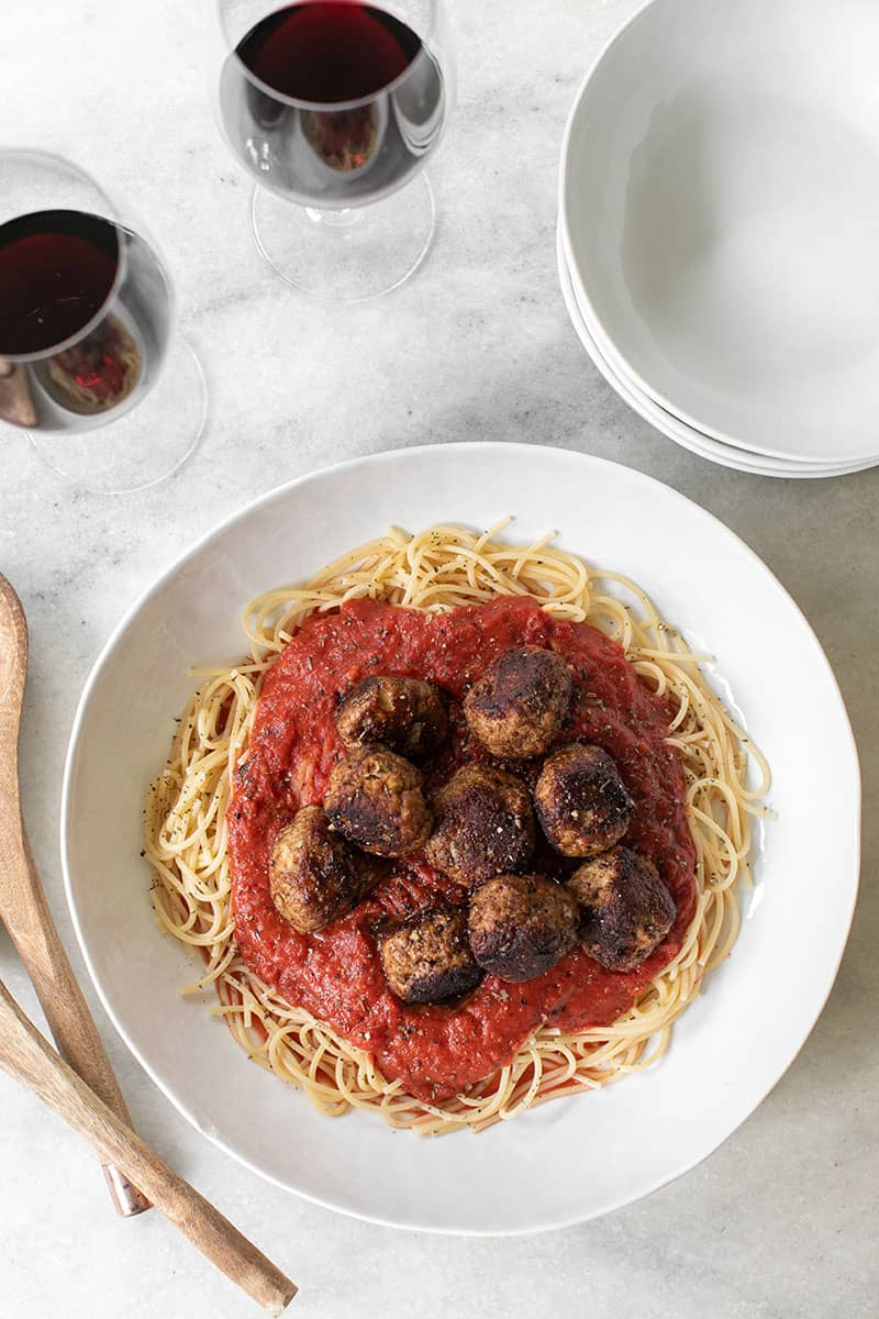 Overhead shot of turkey meatballs and spaghetti in a white bowl.