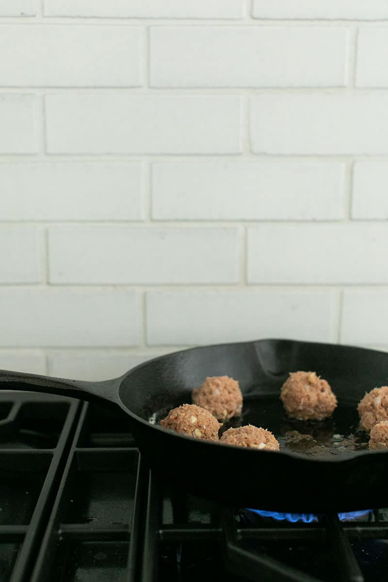 Turkey meatballs cooking in a cast iron pan on a stovetop.