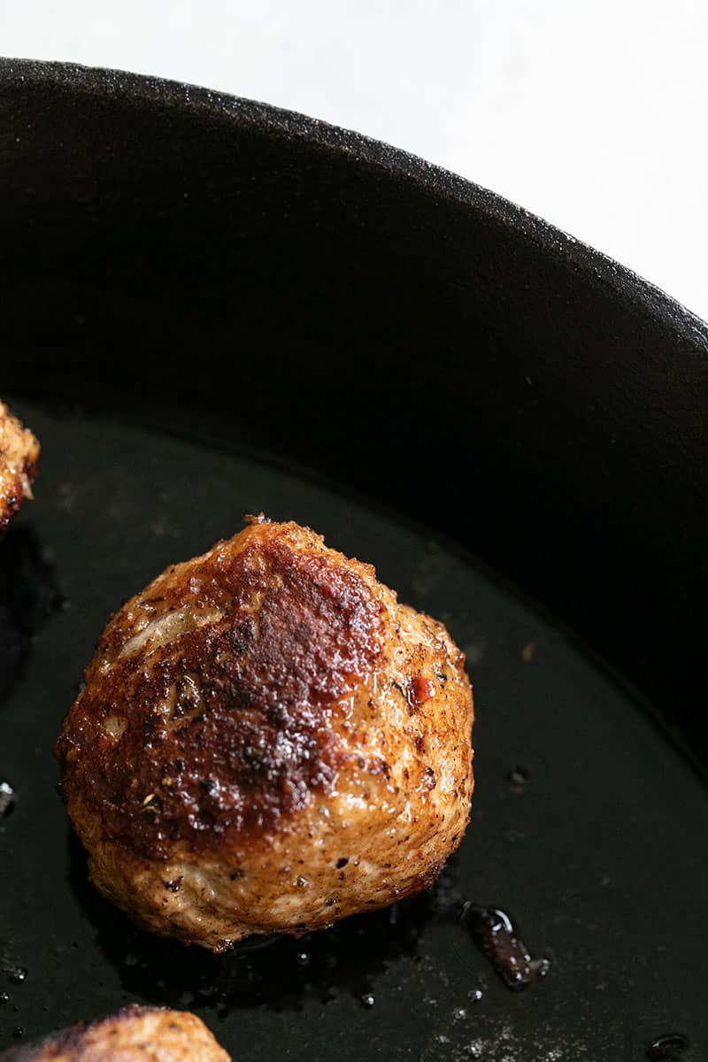 Golden brown turkey meatball in cast iron pan.