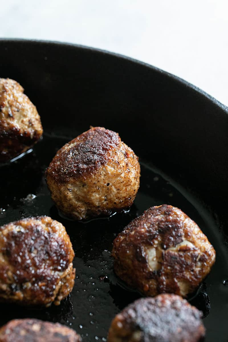 Golden brown turkey meatballs in a cast iron pan.