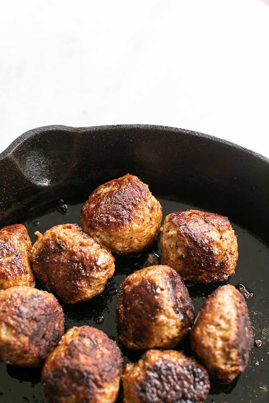 Golden brown meatballs in a cast iron pan.