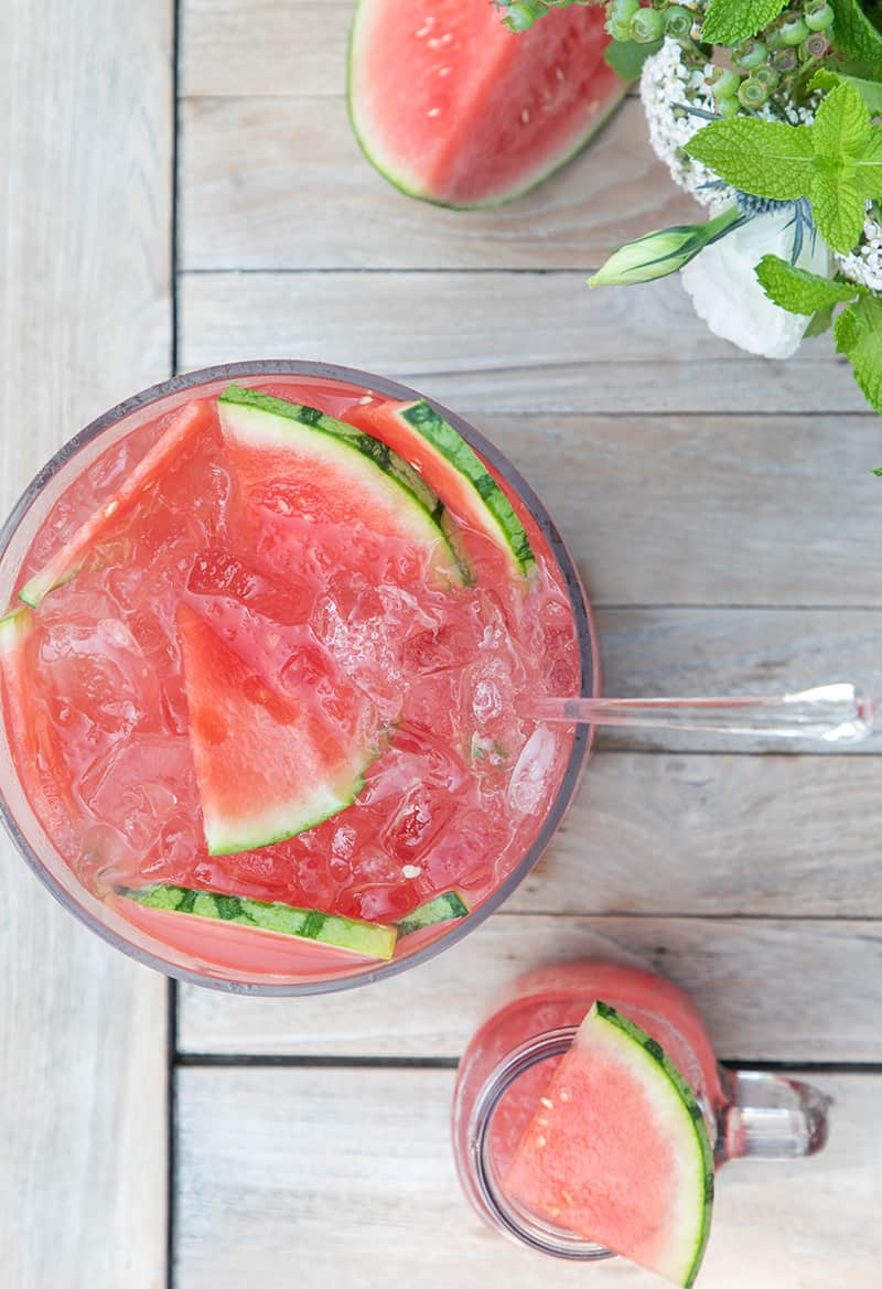 Large glass bowl full of watermelon punch on a wooden table.