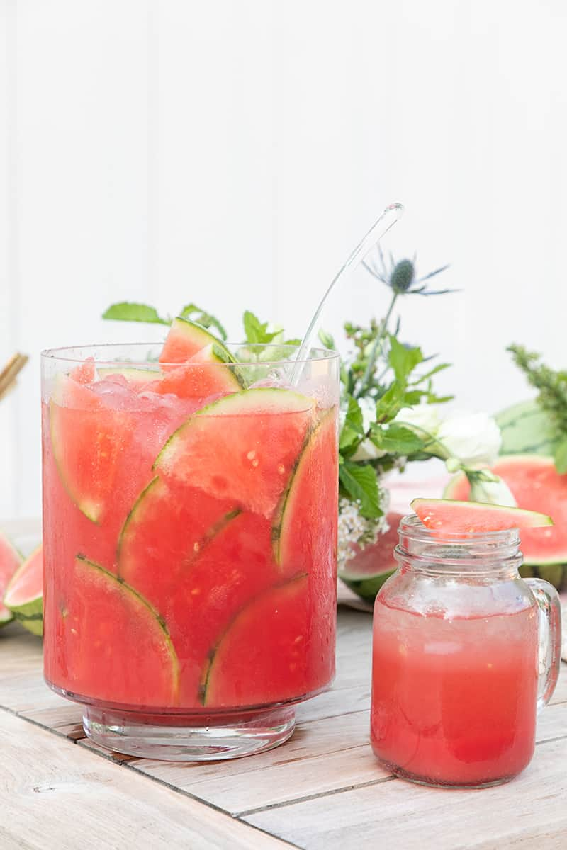 Watermelon punch in large glass pitcher with watermelon slices.