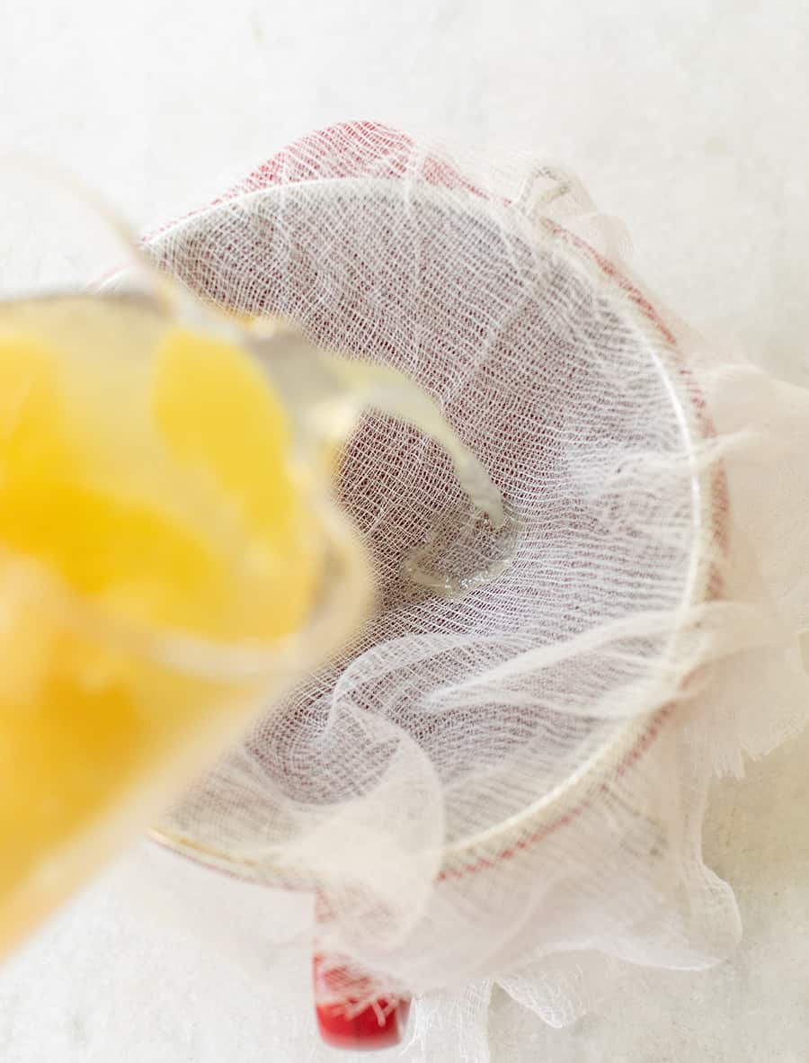 Limoncello being poured into a cheesecloth.