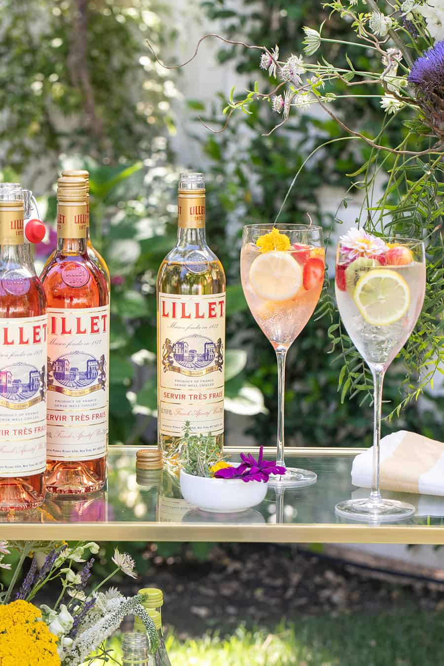Bottle of Lillet on bar with wine glasses.